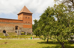 Lida, Belarus - July 11, 2016: Stone building takes the form of misuse of the quadrilateral with two corner towers. In front there Royalty Free Stock Photography
