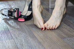 Lidande för den unga kvinnan från ben smärtar på grund av obekväma skor, höga häl Fotografering för Bildbyråer