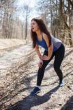 Lidande för den unga kvinnan från smärtar i hennes knä Uppvärmning för jogg royaltyfri foto