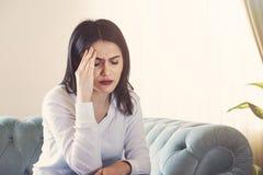 Lidande för den unga kvinnan från stark huvudvärk eller migrän som sitter hemmastatt millennial grabbkänslarus och, smärtar att t royaltyfria foton