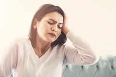 Lidande för den unga kvinnan från stark huvudvärk eller migrän som sitter hemmastatt millennial grabbkänslarus och, smärtar att t royaltyfri bild