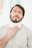 Lidande för den unga mannen från hals smärtar med stängda ögon Fotografering för Bildbyråer