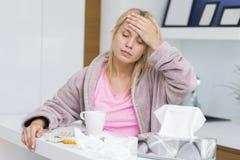 Lidande för ung kvinna från huvudvärk och förkylning Royaltyfria Bilder