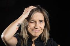 Lidande för ung kvinna från klåda, når tuggor och att ha tryckt på för mygga hennes huvud, i en svart bakgrund Royaltyfri Bild