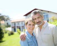 Liddle-gealterte Paare, die auf Front des Hauses stehen lizenzfreies stockbild