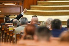The lider of a parliamentary group signals to his coleagues. BUCAREST, ROMANIA - JULY 4, 2018: The lider of a parliamentary group signals to his coleagues how to royalty free stock photo