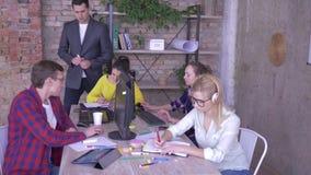 Lider zespołu nauczania praktykanci wyjaśnia pracę i wskazuje przy ekranem komputerowym w nowożytnym biurze, zdjęcie wideo