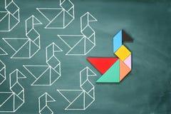 A liderança e o conceito da faculdade criadora com tangram confundem o leadi do pássaro foto de stock royalty free