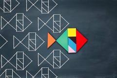 A liderança e o conceito da faculdade criadora com tangram confundem os peixes que conduzem sobre o fundo do quadro Fotos de Stock