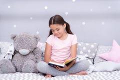 Lido antes do sono A criança da menina senta a cama com o livro lido do urso de peluche A criança prepara-se para ir para a cama  imagens de stock