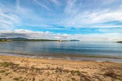 Lido del Sole in Sardinia, Italy. Bocca Island Lighthose as seen from Lido del Sole beach in Sardinia, Italy stock photo