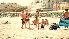 LIDO DI JESOLO, ITALY - AUGUST 8, 2017. Young people socialize on the sandy beach. LIDO DI JESOLO, ITALY - AUGUST 8, 2017. Young people socialize on the beach Royalty Free Stock Images