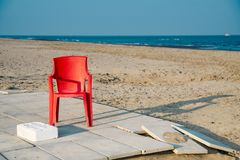 Empty red plastic chair on beach of Lido di Spina, Italy. Lido di Spina, Italy: red plastic chair from the Baywatch on and empty beach. Sunny day, coastline blue royalty free stock photos