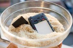 Ließ Ihr Telefon in wasser- die Verlegenheit ist Reis fallen stockbild