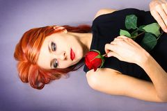 Lie. Beautyful girl lieng with red rose Royalty Free Stock Photo