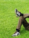 Lie back in grass. A person resting on grass, only his crossed legs with sport shoes on are visible Stock Images