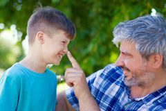 Lie detecting father pushing sons nose. Father pushing sons nose in park, lie detection Stock Photos