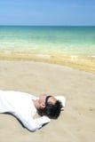 Lie down on tropical beach. Man lie down on tropical beach sand Stock Images