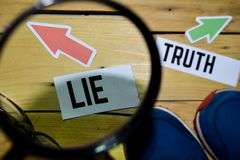 Lie or Truth opposite direction signs in magnifying with sneakers and eyeglasses on wooden stock photography