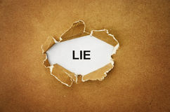 Lie. The word lie in the hole of brown paper Royalty Free Stock Image