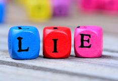 Lie word on table. Lie word on wooden table Royalty Free Stock Images