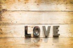 Liebe buchstabiert heraus auf hölzernem Hintergrund Stockfotos