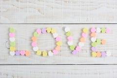 Liebe buchstabiert mit Süßigkeits-Herzen stockbild