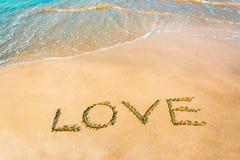 LIEBE, die auf dem Strand mit Welle, Kopienraum beschriftet stockfotografie