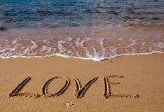 Liebe - die Beschreibung auf dem Sand nahe Meer Stockbilder