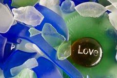 Liebe gedruckt auf einem Glasstein Stockfotos
