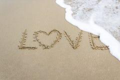 Liebe geschrieben auf goldenen sandigen Strand Lizenzfreie Stockbilder