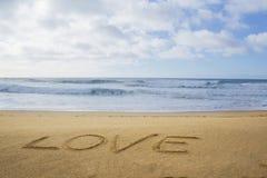 Liebe geschrieben auf Sand stockbild