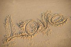 Liebe geschrieben auf Strandsand Stockbild
