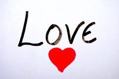 Liebe geschrieben auf weißen Hintergrund mit einem Zeichen stockfotografie