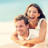 Liebe - glückliches Paar auf dem Strand, der Spaßdoppelpol hat Lizenzfreies Stockfoto