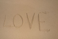Liebe im Sand mit Steinherzen Stockbilder