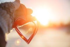 Liebe im Winter Geformtes Symbol Valentine Day des Herzens Herz mit den Händen, Gefühls- und Lebensstilkonzept auf dem Sonnenunte stockbild