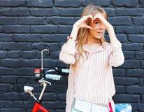Liebe Lächelnde glückliche junge Frau des Nahaufnahmeporträts mit langem blon Haar, Herzzeichen machend, Symbol mit den Händen po Stockbilder