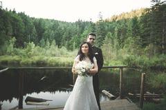 Liebe und Leidenschaft - Kuss von verheirateten jungen Hochzeitspaaren nähern sich See Lizenzfreie Stockfotos