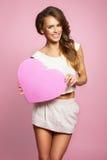 Liebe und Valentinsgrußtagesfrau, die das Herzlächeln nett halten und entzückendes lokalisiert auf rosa Hintergrund Stockbild