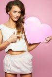Liebe und Valentinsgrußtagesfrau, die das rosa Herzlächeln nett halten und entzückendes lokalisiert auf rosa Hintergrund Stockbild