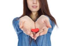Liebe und Valentinstag schöner Brunette, der ein rotes Herz in den Händen lokalisiert auf weißem Hintergrund hält Stockbild