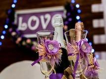 Lieben Sie Aufschrift auf einem hölzernen Hintergrund, Blinklichter, Blumen Flasche Champagner und Gläser Lizenzfreies Stockfoto