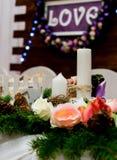 Lieben Sie Aufschrift auf einem hölzernen Hintergrund, Blinklichter, Blumen Kerzen und Niederlassung der Kiefer Stockbild