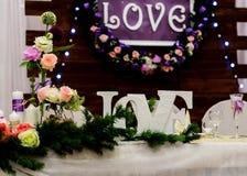 Lieben Sie Aufschrift auf einem hölzernen Hintergrund, Blinklichter, Blumen Kerzen und Niederlassung der Kiefer Stockbilder