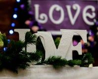 Lieben Sie Aufschrift auf einem hölzernen Hintergrund, Blinklichter, Blumen Kerzen und Niederlassung der Kiefer Lizenzfreie Stockfotos