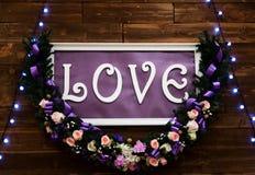 Lieben Sie Aufschrift auf einem hölzernen Hintergrund, Blinklichtern und Blumen Dekorative künstlerische Animation gewidmet  Stockfoto