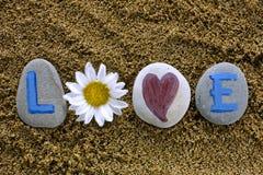 Lieben Sie Bann heraus von den Steinen mit Buchstaben, Herzen und Blume Stockfotografie