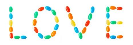 LIEBEN Sie das Beschriften gemacht von den mehrfarbigen Süßigkeiten, die auf Weiß lokalisiert werden Stockbild