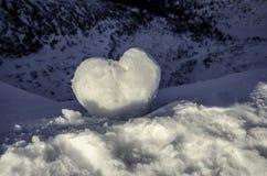 Lieben Sie das Herz, das vom Schnee auf den Hügel gemacht wird Stockfotos
